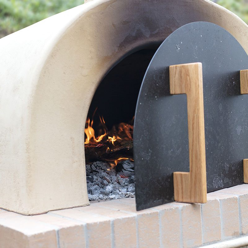 Pizza oven made of brick, cement and tile being prepped for baking pizza with firewood